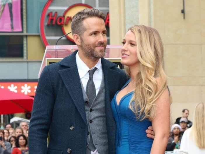 Ryan Reynolds in a three-piece suit on the left, Blake Lively in a blue dress on the right.