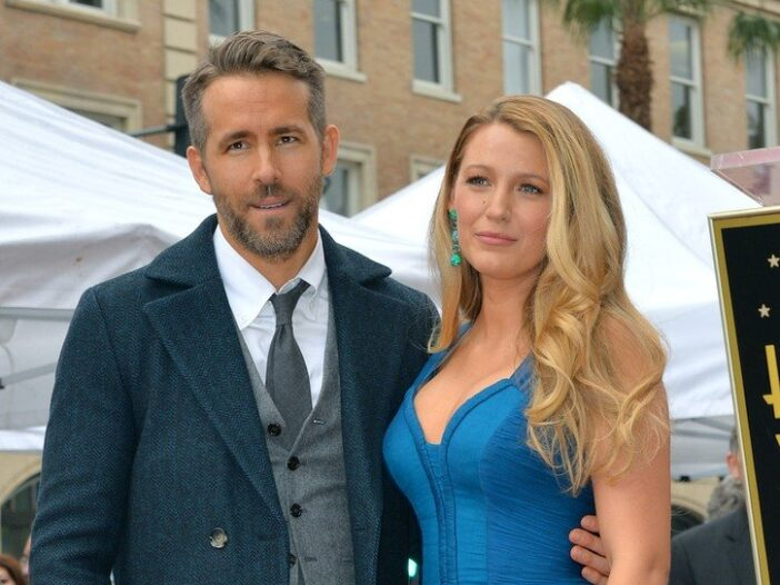 Ryan Reynolds in a three piece suit stands outside with wife Blake Lively in a blue dress