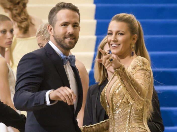 Ryan Reynolds on the left in a tuxedo, Blake Lively on the right in a gold dress, both laughing and pointing towards the camera.