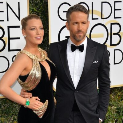 Ryan Reynolds smiling in a tuxedo with arm around Blake Lively in a black and gold dress