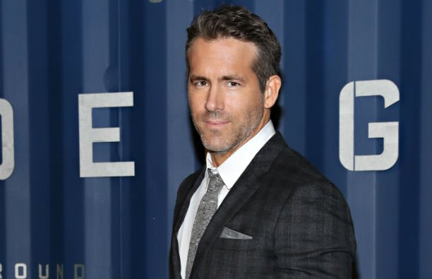 Ryan Reynolds wearing a patterned, dark suit on the red carpet.