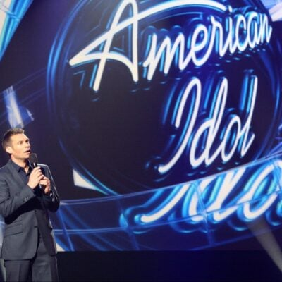 Ryan Seacrest making an announcement on stage at an American Idol event