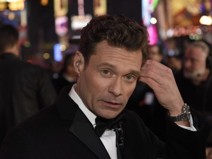 Ryan Seacrest wearing a black tux during New York's New Year's Eve celebration.