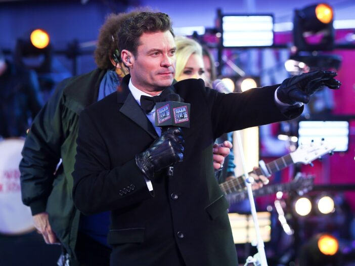 Ryan Seacrest wearing a black coat and holding a microphone on New Year's Eve in New York City.