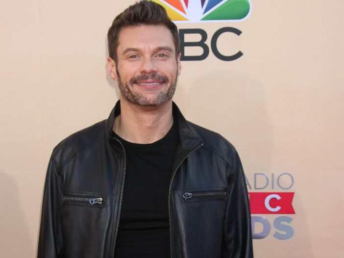 Ryan Seacrest wearing a black t-shirt and leather jacket to the iHeart Music Awards red carpet