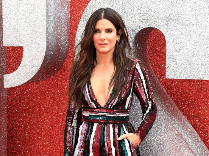 Sandra Bullock with her left hand in her pocket in a colorful dress.