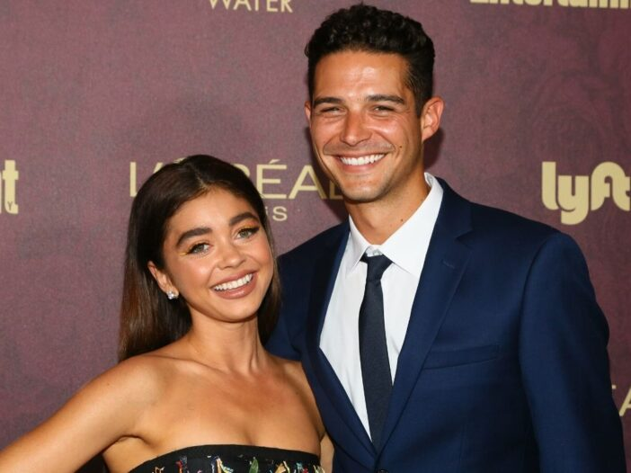 Sarah Hyland wearing a black dress standing with Wells Adams, who's wearing a dark suit, on the red