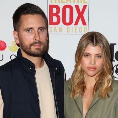 Scott Disick in a tan long sleeve shirt and black vest stands next to Sofia Richie in a green jumper