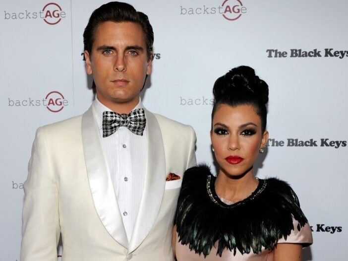 Scott Disick in a white suit standing with Kourtney Kardashian, who's wearing a pink dress with a bl