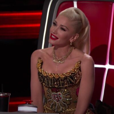 Screenshot from The Voice of Gwen Stefani in a gold dress sitting on a red coach chair