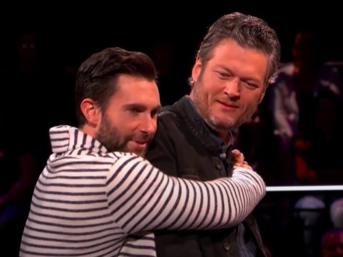 Screenshot from The Voice of Adam Levine in a striped hoodie hugging Blake Shelton
