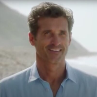 Screenshot of Grey's Anatomy with Patrick Dempsey smiling in a light blue shirt on a beach