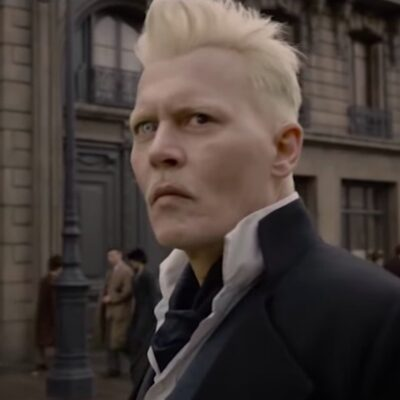 Screenshot of Johnny Depp in a black suit standing outside in Fantastic Beasts