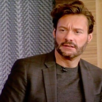 Screenshot of Live with Ryan Seacrest in a dark suit and shirt on set