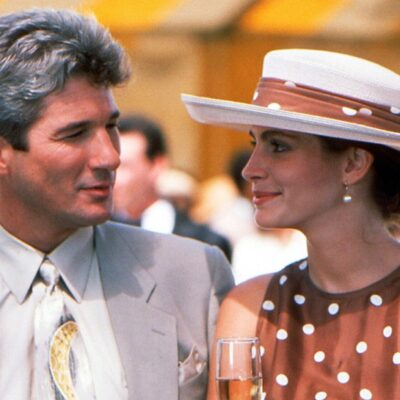 Screenshot of Pretty Woman, Richard Gere on the left in a light grey suit, Julia Roberts in a brown polka-dotted dress and hat.