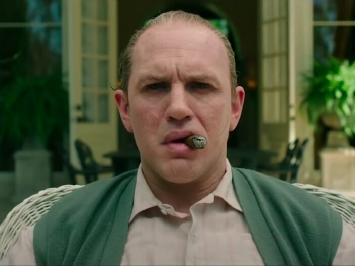 Screenshot of Tom Hardy with a cigar in his mouth as Al Capone in the film Capone