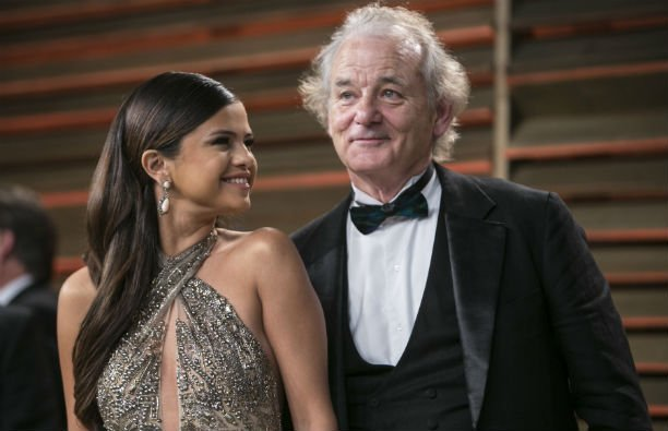 Selena Gomez in a metallic dress standing near Bill Murray, who's wearing a black tux, at the Vanity