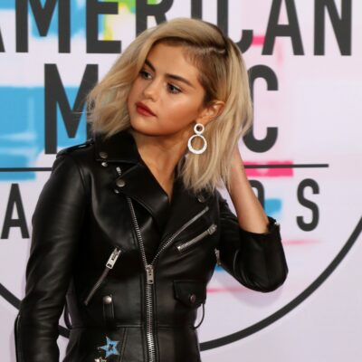 Selena Gomez wearing a black, leather-like dress to the American Music Awards