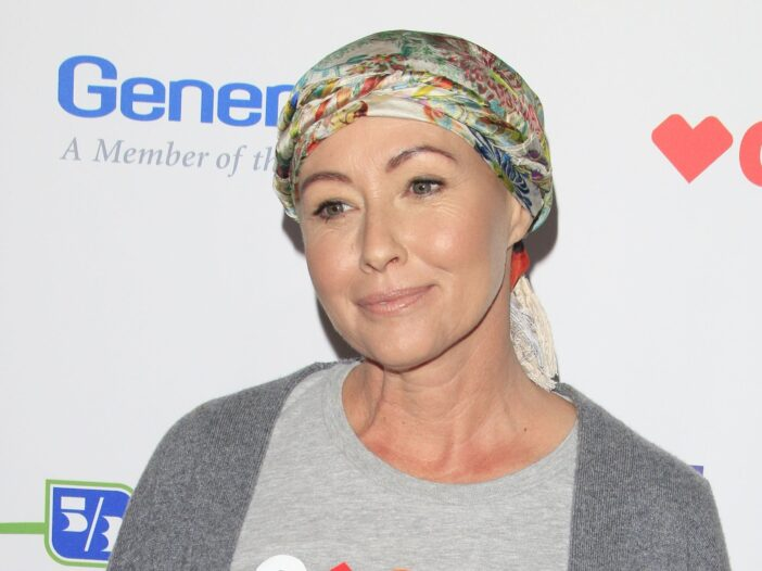 Shannen Doherty wearing a gray Stand Up 2 Cancer shirt under a darker gray cardigan