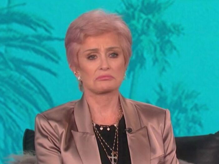 Sharon Osbourne wearing a tan satin blazer, black shirt, gold necklaces and sporting a frown while on _The Talk_.