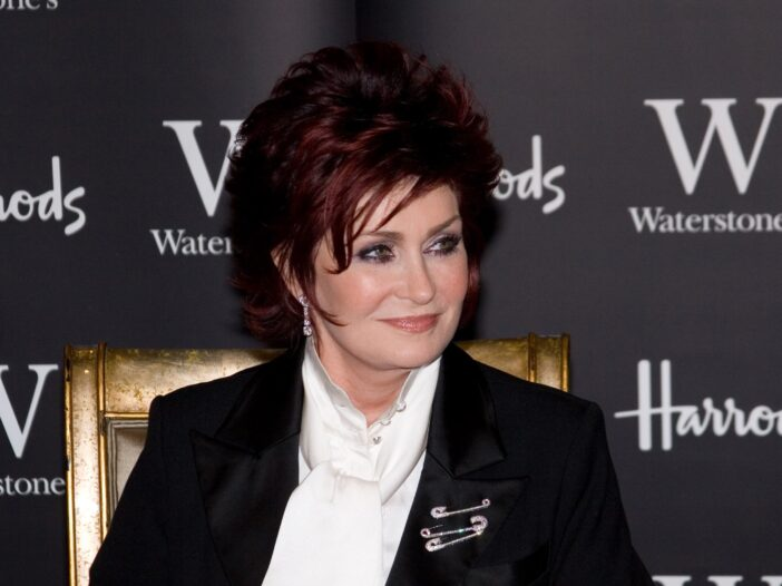 Sharon Osbourne with red hair and a dark jacket over a white shirt.