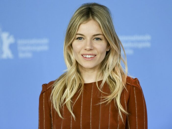 Sienna Miller in a brownish-orange top, standing in front of a blue background.