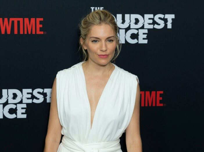 Sienna Miller smiling in a white dress