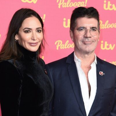 Simon Cowell in a suit standing with Lauren Silverman in a black dress