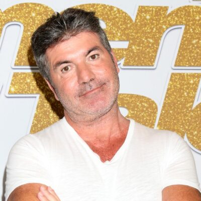 Simon Cowell in a white t-shirt looking annoyed.