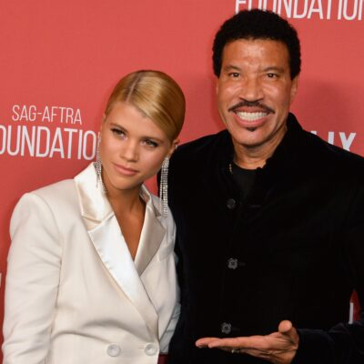 Sofia Richie wearing a white suit and standing with her father, Lionel Richie, who's in a black suit