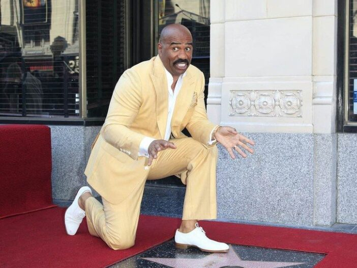Steve Harvey smiles in a yellow suit while kneeling in front of his Hollywood Blvd star.