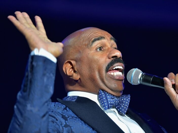 Steve Harvey wearing a blue tux onstage at the 2015 Ford Neighborhood Awards
