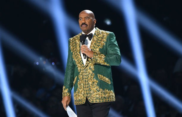 Steve Harvey wearing a green and gold suit jacket at the Miss Universe pageant