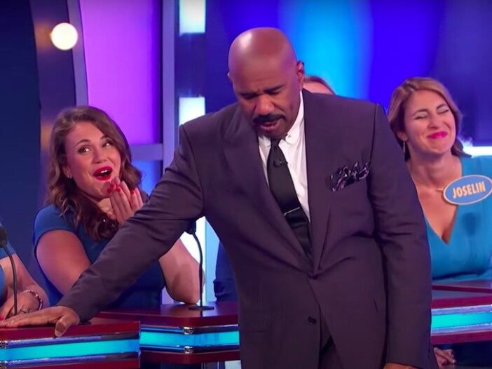 still from Family Feud of Steve Harvey in a suit grimacing and looking down
