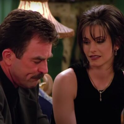 still from Friends of Courteney Cox in a black dress looking at Tom Selleck in a suit