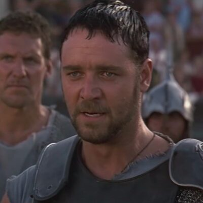 still from Gladiator of Russell Crowe in black armor without a helmet on surrounded by gladiators