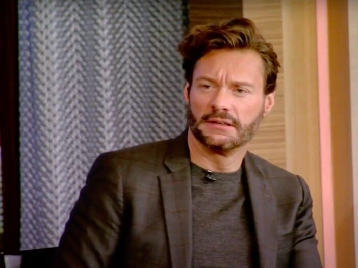 still from Live with Kelly and Ryan of Ryan Seacrest in a brown suit looking confused