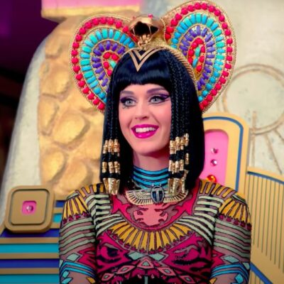still of Katy Perry smiling in a colorful Egyptian-inspired costume for the Dark Horse music video