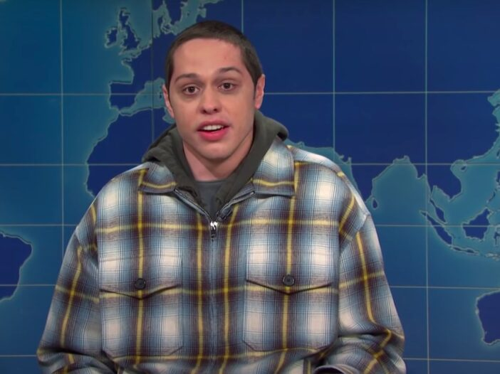 still of Pete Davidson with his mouth open in a plaid hoodie on Saturday Night Live