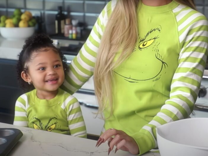 Stormi Webster stands by her mom, Kylie Jenner in their kitchen wearing matching Grinch pajamas
