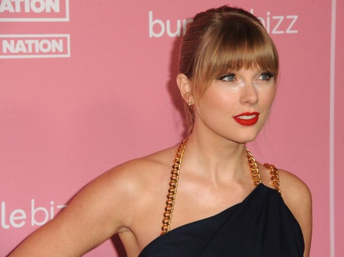 Taylor Swift in a black dress with a gold strap.
