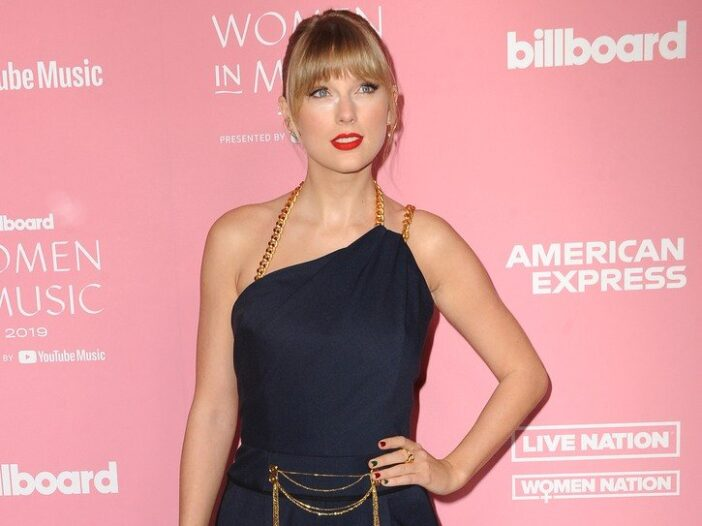 Taylor Swift in a dark outfit with gold straps.