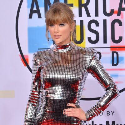 Taylor Swift in a sparkling mirrored dress, with her left hand on her hip.