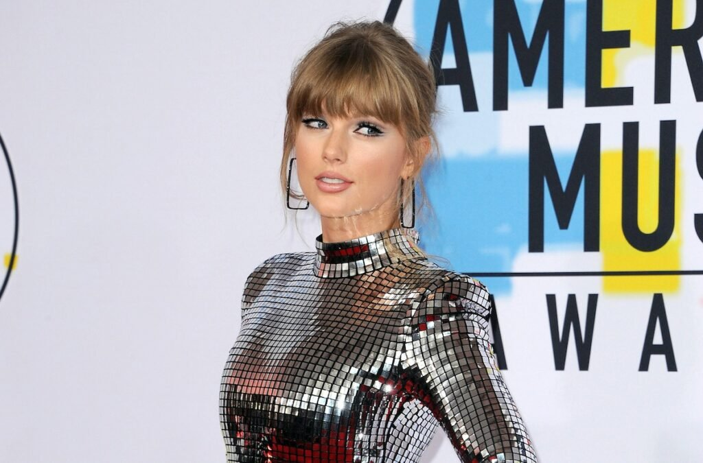 Taylor Swift smiling in a shiny silver dress