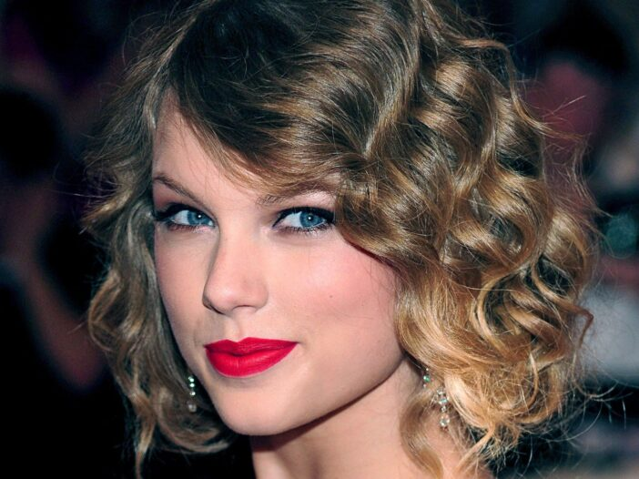 Taylor Swift wears her curly blonde hair in an updo on her way into a gala