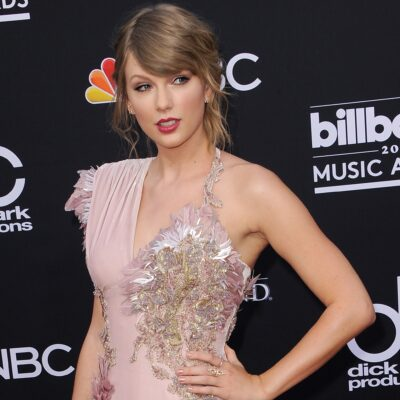 Taylor Swift with her left hand on her hip in a pink dress.