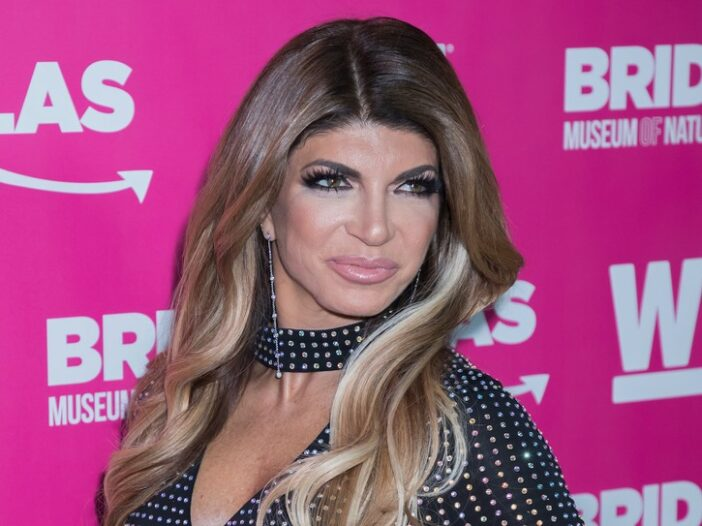Teresa Giudice in a black outfit against a pink background