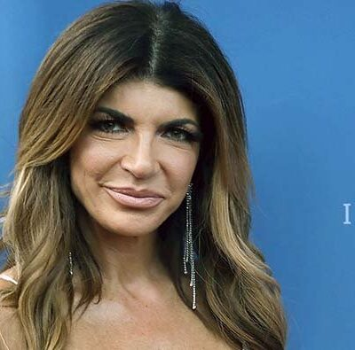 Teresa Giudice in a gold dress on a red carpet