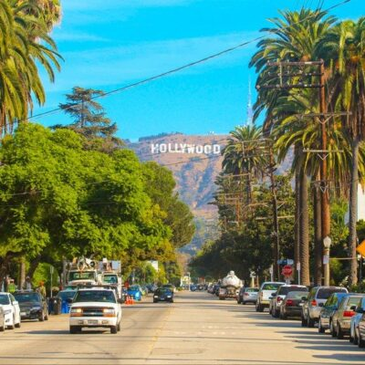 The Hollywood Hills and the famous Hollywood sign loom over a street in Los Angeles