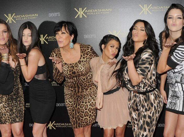 The Kardashian/Jenner sisters standing with Kris Jenner on the red carpet
